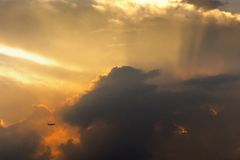 Flight in sunset cloud. A airplane is flying through the dark clouds with sunset Royalty Free Stock Photography