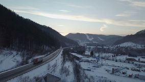 Aerial view of sunset over high way in winter. Flight at sunset over road with cars and truck by industrial zone in snowy winter country. Aerial view fly down stock footage