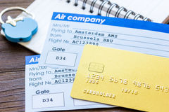 Flight tickets payment online with cards on wooden table. Flight tickets payment online with credit cards and copybook on dark wooden table background Royalty Free Stock Photography