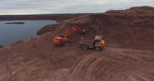 Flight to drone on sand quarry. With heavy machinery, the old truck and excavator. loading sand excavating in heavy trucks stock footage
