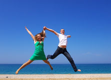 Flight together. Two people happily jump on beach Stock Image