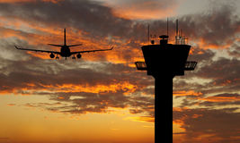 Flight tower and plane. Silhouette flights and sunset background Royalty Free Stock Images