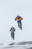 Flight two riders on motorcycles after jump from hill Stock Images