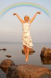 Flight under rainbow. Lovely blond jumping at the seashore under colorful rainbow Stock Photo