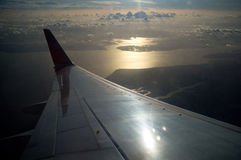 Flight wing in the air. A view of a plane wing through the plane window in the air Royalty Free Stock Photos