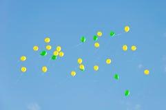 Flight yellow and green small balloons Royalty Free Stock Photos