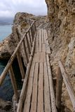 Flimsy old rotten bridge across the rocks on the sea coast Royalty Free Stock Image