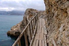 Flimsy old rotten bridge across the rocks on the sea coast Stock Photo