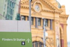 Flinders Street Station sign with Flinders Street Station in the. Flinders Street Station direction sign with Flinders Street Station in the background Royalty Free Stock Images