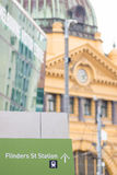 Flinders Street Station sign with Flinders Street Station in the Stock Photo