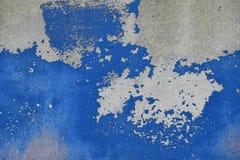 Flingor av gamla blått målar på den gråa betongväggen Royaltyfri Bild