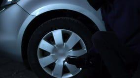 Flinker Dieb, der Autoreifen und Räder auf schlecht vorsichtigem Parkplatz, Verbrechen stiehlt stock footage