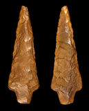 Flint Arrowhead - Front and Back. Macro photography of a prehistoric arrowhead in flint stone. Front and back, isolated on black background Stock Photography