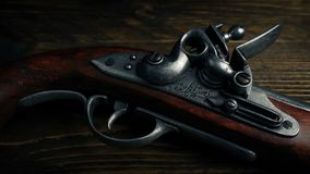 Flintlock pistol on wooden table stock footage
