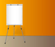 Flip chart with a blank sheet of paper near colored wall in the office. Royalty Free Stock Photography