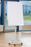 Flip Chart On Hardwood Floor in bianco fotografia stock