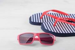 Flip-flop in bande blu e bianche con gli occhiali da sole rossi Accessori della spiaggia immagine stock libera da diritti