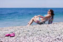 Flip-flop on the beach. Flip-flop and girl on the sea  beach Royalty Free Stock Image