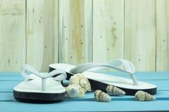 Flip-flop bianchi con gli shellfishs sulla tavola di legno blu fotografia stock