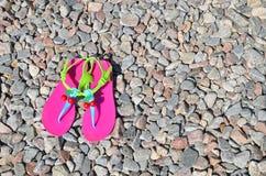 Flip-flop brillantes plásticos en el guijarro Fotografía de archivo libre de regalías