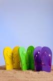 Flip-flop colorido Sandles en una playa de Sandy Imágenes de archivo libres de regalías