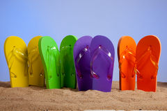 Flip-flop colorido Sandles en una playa de Sandy Imagen de archivo libre de regalías
