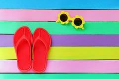 Flip-flop con gli occhiali da sole su fondo di legno variopinto Immagine Stock Libera da Diritti