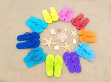 Flip-flop di colore sulla spiaggia sabbiosa Immagine Stock
