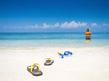 Flip flop and dive equipment on white sand beach Stock Photo