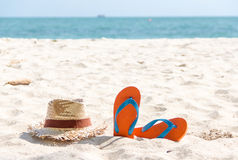 Flip-flop et un chapeau tissé sur la plage. photos libres de droits