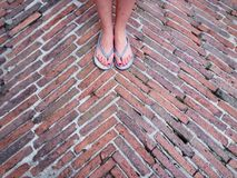 Flip flop feet standing on brick ground Royalty Free Stock Photo