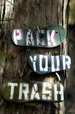 Flip Flop Recycle. Pack your trash instructions are painted on the underside of recycled flip flops.  The flip flops are then nailed to the trees along the Stock Images