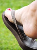 A flip flop. And a red fingernail Royalty Free Stock Images