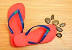 Flip-flop rossi e ciottoli sui precedenti di legno Immagini Stock Libere da Diritti