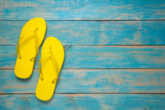 Flip-flop, Sandal, Summer. Yellow Flip Flop Sandals On Blue Wood Royalty Free Stock Image