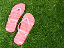 Flip Flop Sandals on Grass Spring Summer. A pair of bright colored flip flop sandals on a grassy background with room for copy on the right stock photo