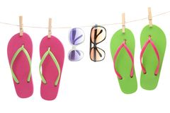 Flip-flop sandles and sunglasses hanging by clips Royalty Free Stock Images