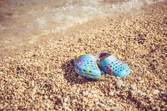 Flip flop by the sea. View to the blue flip flops covered by little stones in the beach by the sea stock images