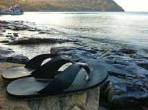 Flip flop shoes put on stone front the beach.  stock image