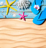 Flip-flop, starfish, seashells and coral on wooden and sand as beach background Stock Images