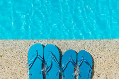 Flip Flop on stone Floor pool edge with surface of water background. Concept of leisure and travel stock photos