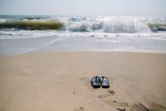 Flip-flop su una spiaggia sabbiosa nelle vacanze estive con il mare d'ondeggiamento fotografie stock