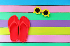Flip flop with sunglasses on colorful wooden background Royalty Free Stock Image