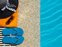 Flip Flop, towel, hat on pool edge with surface Royalty Free Stock Photo
