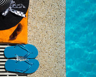 Flip Flop, towel, hat on pool edge with surface Royalty Free Stock Photos