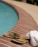 Flip-Flop and a towel by a pool. Towel, sun glasses and worn flip-flops laying beside a pool Stock Image