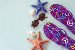 Flip-flop variopinti, stelle marine, coperture ed occhiali da sole su fondo di legno Fotografie Stock
