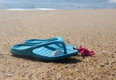 Flip-flop y estrellas de mar rosadas en la playa Foto de archivo