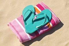 Flip-flop y toalla en la playa. Imagenes de archivo