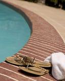 Flip-flop y una toalla por una piscina Imagen de archivo